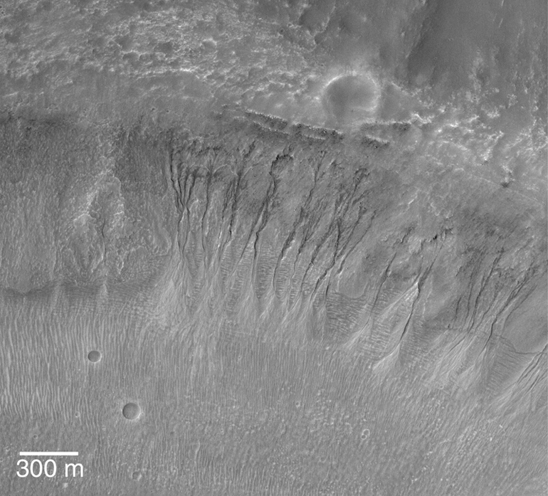 Gullies on an inside crater wall indicates creation by water. Notice the two 'young' impacts craters at the lower right.