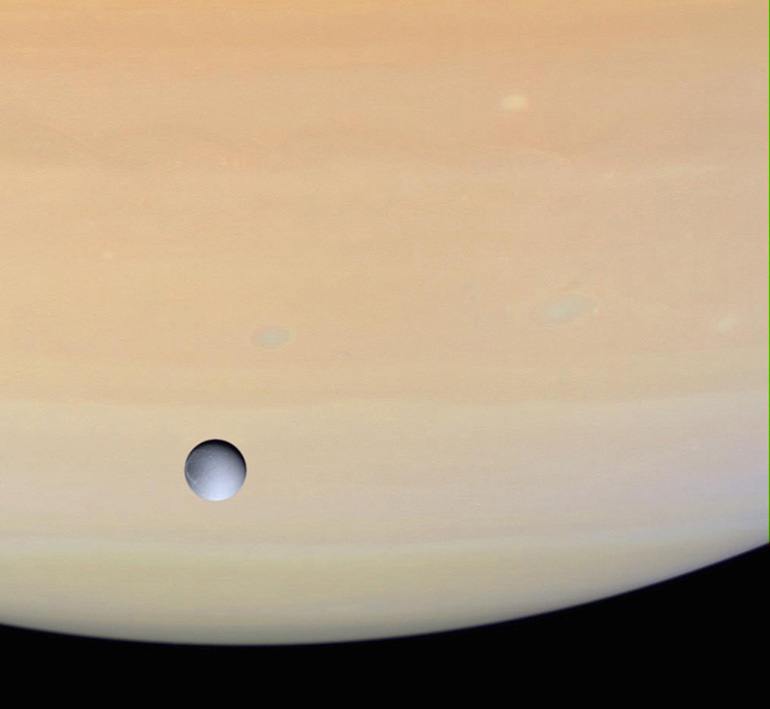 A Cassini image of Dione against Saturn.